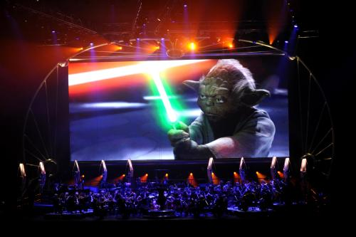 Yoda brandishes a light sabre onscreen over the orchestra during one of the musical segments of Star Wars™: In Concert.