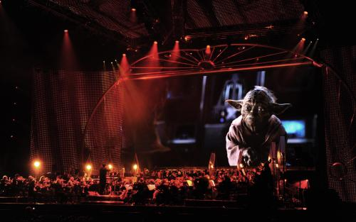 A contemplative Yoda onscreen over the orchestra during Star Wars™: In Concert.
